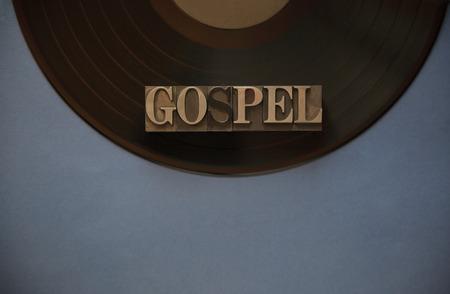 テキストの青灰色の背景に黒のビニール レコードの古い金属タイプの福音」という言葉