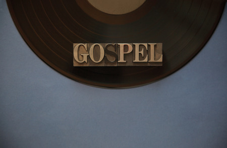 The word gospel in old metal type on a black vinyl record with a blue-gray background for text Reklamní fotografie