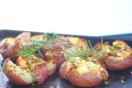 Smashed, roasted potatoes with rosemary and coarse salt on metal pan with copy space