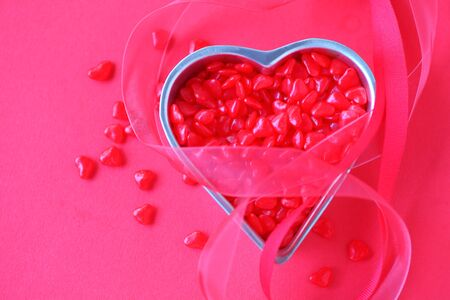 hots: Small heart container filled with tiny red candies with red ribbons and room for text