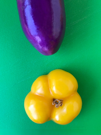 A purple eggplant and yellow bell pepper half on a green background