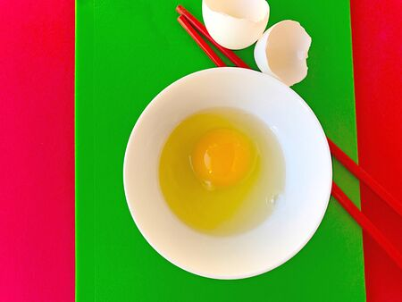 uncluttered: Raw egg in white bowl with red chopsticks and eggshells on green and red cutting boards Stock Photo