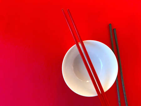 White Chinese bowl with red and black chopsticks on a red background Stock Photo