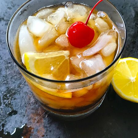 Closeup of whiskey sour cocktail with lemon, crushed ice and a maraschino cherry