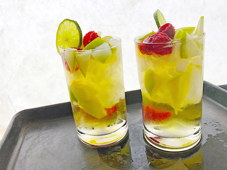 Two white wine coolers with fresh raspberries, green apple chunks and lime with copy space