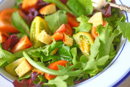 Mixed greens salad with miniature heirloom tomatoes and croutons Stock Photo