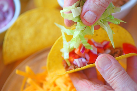adds: A man adds shredded lettuce to a homemade taco closeup