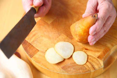 A man cuts a fresh pear into very thin slices on a wood cutting board Stock Photo