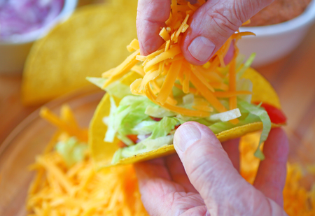 adds: A man adds grated cheese to his homemade taco Stock Photo