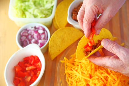 Overhead of a man making tacos with ground beef, tomatoes, onions, lettuce and grated cheese alongside