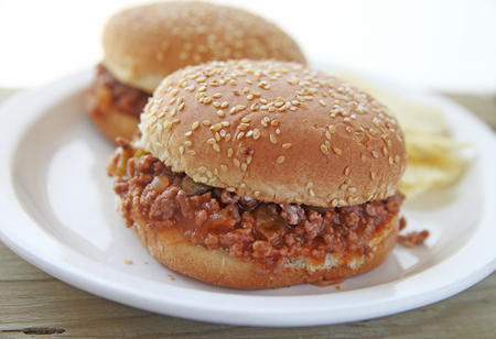 Two sloppy joe sandwiches on sesame seed buns with potato chips and room for text