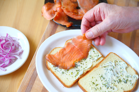 A man puts together a sandwich of smoked salmon and onion on bread with herb mayonnaise Stock Photo