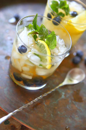 Two glasses of green tea with crushed ice, lemon, fresh blueberries and mint leaves