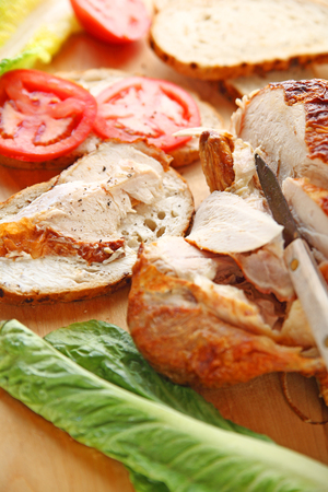 Cutting roast chicken into slices for sandwiches with lettuce and tomatoes