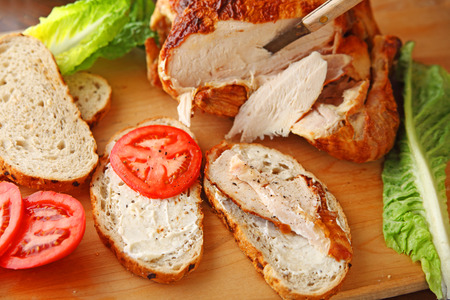 Slicing up a store-bought rotisserie roast chicken for sandwiches on rye bread with lettuce and tomatoes Stock Photo
