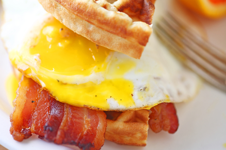 Sandwich of waffle, bacon and fried egg with yolk broken Imagens - 88622120
