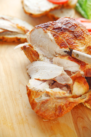 a purchased rotisserie roast chicken with knife on cutting board with room for text