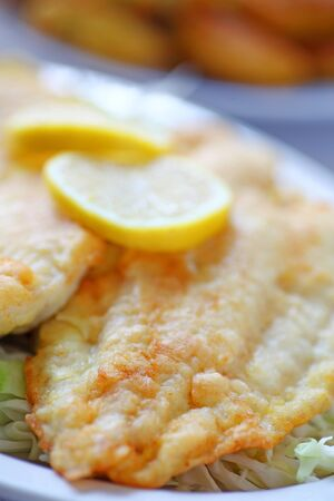 Closeup of fried catfish with lemon slices