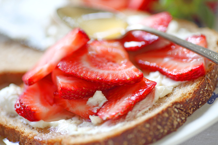 Sliced strawberries with cream cheese on whole wheat bread with honey Stock Photo