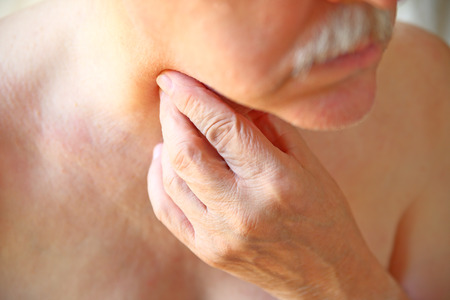 An older man touches his painful throat with his fingers