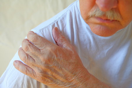 Senior man in a white t-shirt with his hand on a painful shoulder