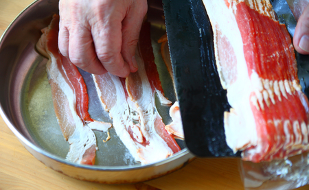 An older man prepares bacon for frying