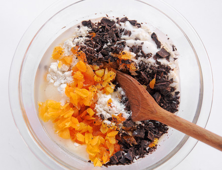 Overhead view of dark chocolate pieces, chopped dried apricots and flour in a glass mixing bowl 写真素材