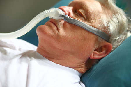 Older man with breathing apparatus for sleep apnea