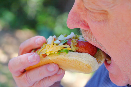 A senior man bites into a hot dog topped with raw onions, relish, lettuce and grated cheese