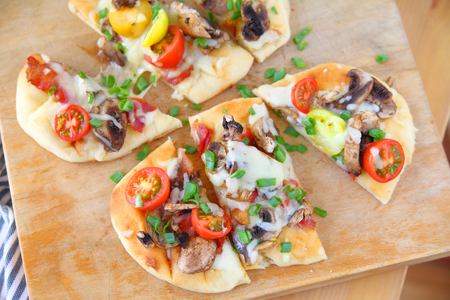 Naan pizzas with cherry tomatoes, mushrooms, bacon and scallions cut into portions