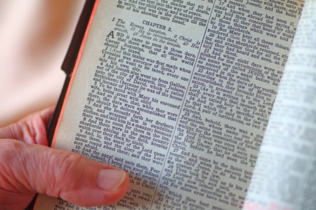 Senior man reading Christmas story in a vintage Bible