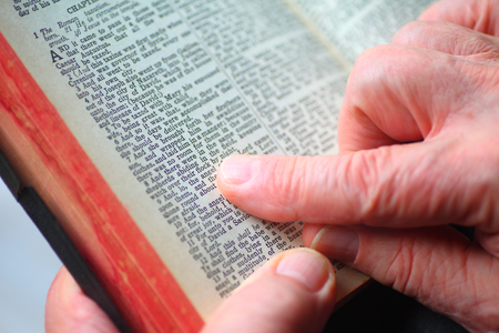 A senior man holds a vintage Bible and uses his fingers to track the words 写真素材