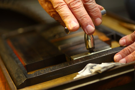 Closeup of ink-stained fingers of man using a quoin key to prepare type for letterpress printing