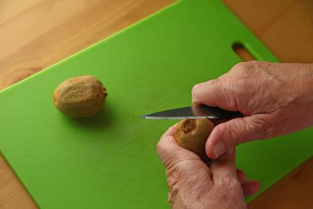 An older man peels a kiwifruit over a green cutting board