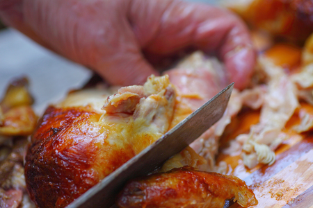 Man grasps chicken, using a kitchen knife to cut off pieces