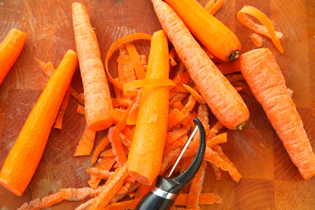 Several carrots with a peeler