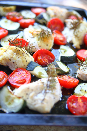 Sheet pan meal of boneless chicken pieces, cherry tomatoes and zucchini with rosemary Banque d'images