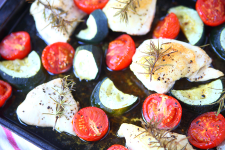 Overhead view of boneless chicken, zucchini and cherry tomatoes on baking pan Banque d'images