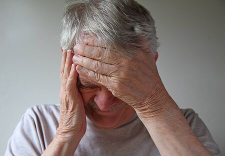 Older man with his hands on forehead and side of face