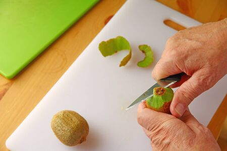 Overhead view of older man peeling kiwifruit with room for text Banque d'images