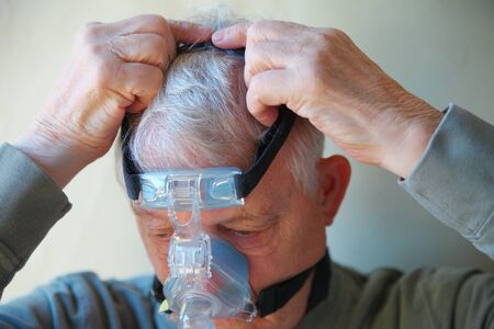 Senior patient with sleep apnea treatment machine head gear