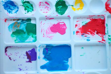 Acrylic paint in various colors on a plastic palette