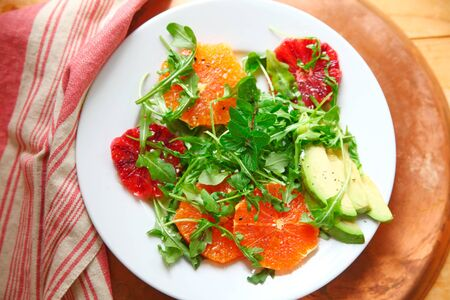 Caracara and blood oranges with baby greens and avocado on a white plate