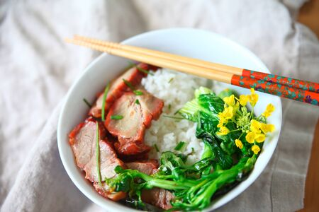 Roast pork and Asian greens with edible flowers on rice