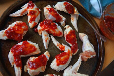 Raw chicken wings with spoonful of barbecue sauce  Banque d'images