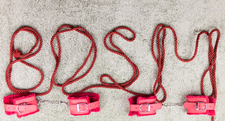 BDSM. The letters are laid out of the rope for bindings (shibari). Zdjęcie Seryjne