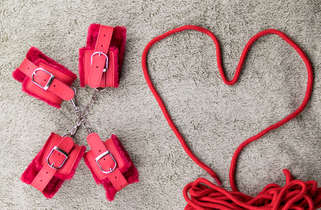 Red handcuffs and a rope for binding lined in the shape of the heart. Stock Photo
