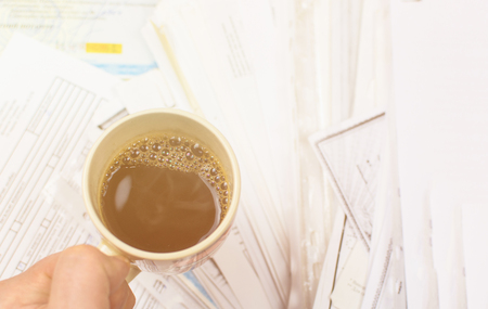 Deadline written on paper and a cup of coffee in hand against a background of scattered papers. Toned.