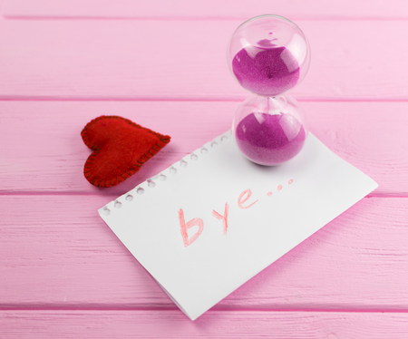 End of love. Hourglass and the word bye on a piece of paper with a heart next to it.