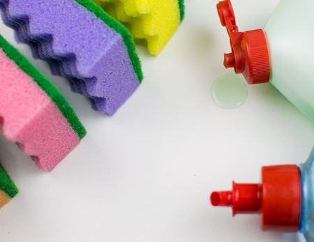 Multicolored foam rubber sponges and detergent on a light background.